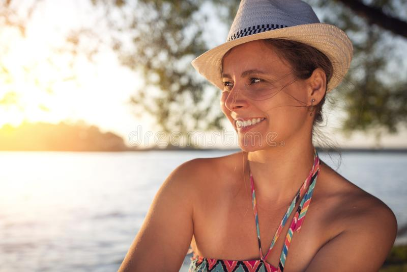 La belle dame bronzée heureuse de sourire dans le chapeau d'été sur le lac étayent sur le fond du coucher du soleil au-dessus de  photographie stock libre de droits