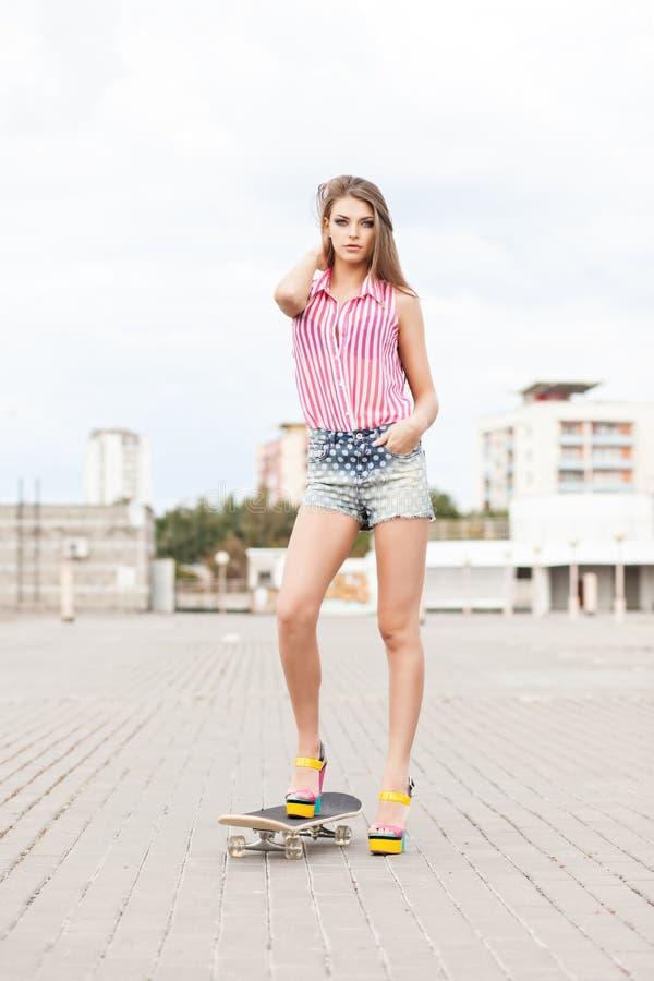 La belle dame dans des shorts courts de jeans se tient sur la planche à roulettes photographie stock