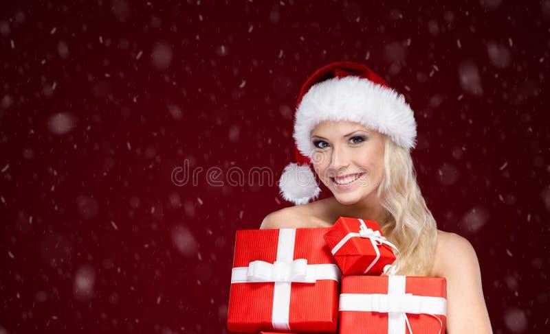 La belle dame dans le chapeau de Noël tient un ensemble de présents images libres de droits
