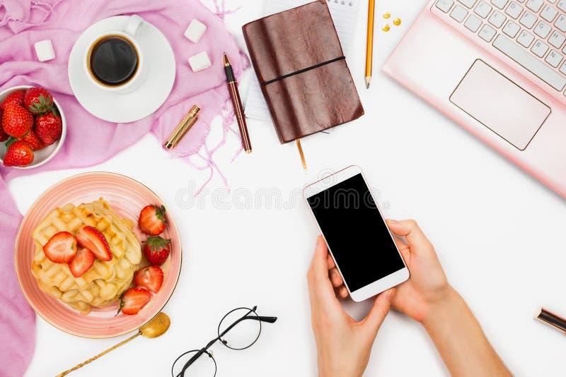 La belle disposition flatlay avec la tasse de café, les gaufres chaudes avec de la crème et des fraises, l'ordinateur portable et photo stock