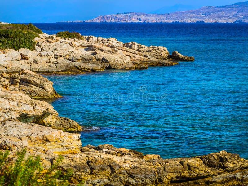 La belle eau bleue claire et plage cachée rocheuse image stock
