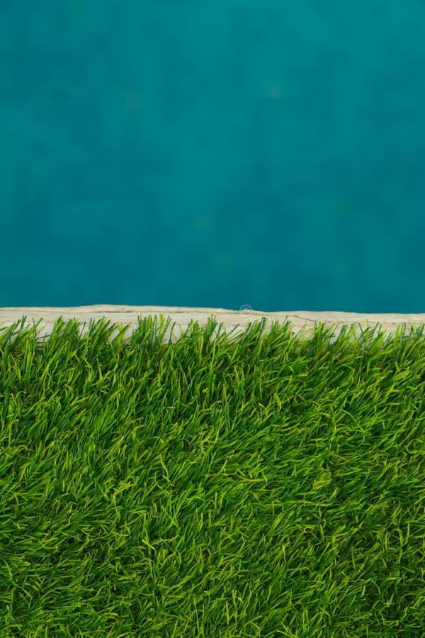 La belle eau bleue et herbe de vert artificielle de gazon wallpaper images stock