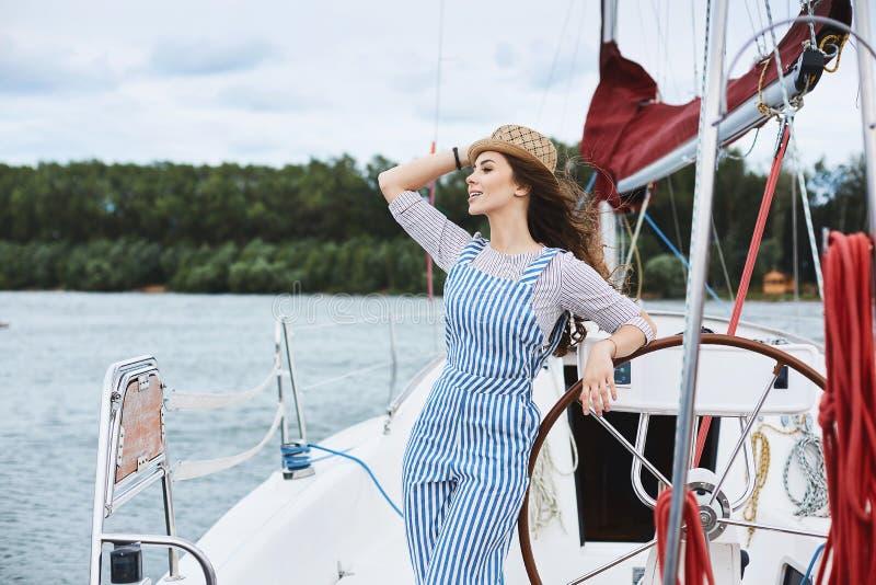 La belle et à la mode fille de modèle de brune dans des combinaisons rayées blanches et bleues élégantes et dans un chapeau, la j photographie stock