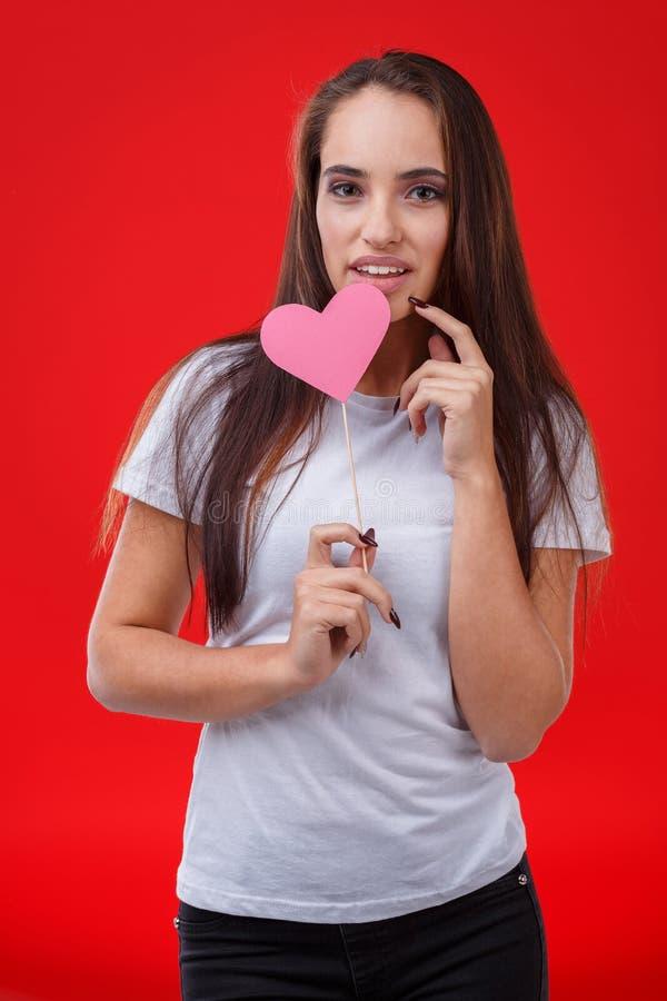 La belle et mignonne fille, prises un coeur de papier rose sur un bâton a légèrement séparé la bouche Fond rouge photo stock