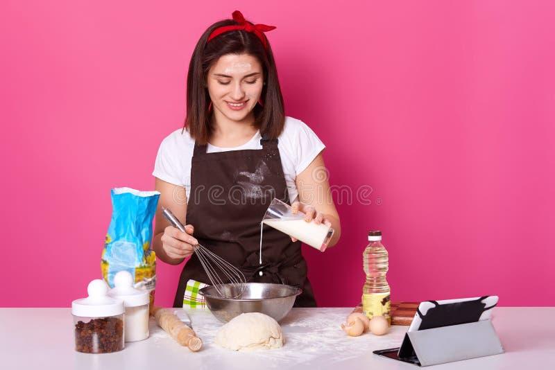 La belle femelle de brune verse le lait dans le plat Le chef malaxe la p?te, se pr?parant aux vacances de P?ques, faisant les pet photos libres de droits