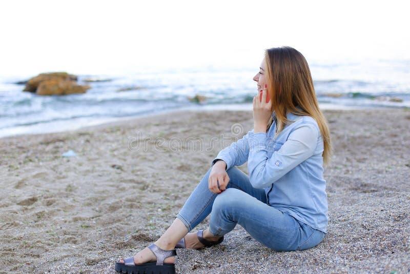 La belle femelle parle du mobile avec le sourire et s'assied sur la plage n photo stock