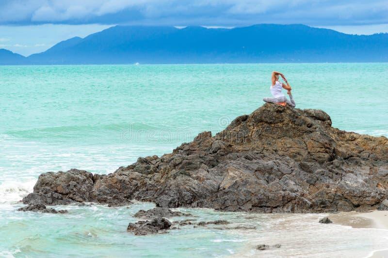 La belle femme âgée mûre s'assied sur une falaise faisant le yoga photo libre de droits