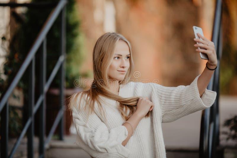 La belle femme élégante blonde occasionnelle de mode avec un téléphone dans sa main font le selfie Bâtiments et rue européens sur image libre de droits