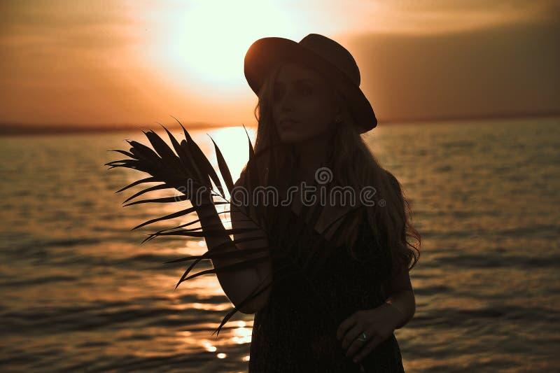 La belle femme élégante dans le chapeau avec la palmette dans des mains a un amusement sur la plage au coucher du soleil images stock