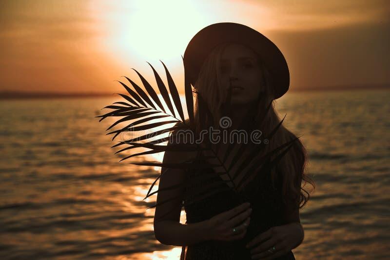 La belle femme élégante dans le chapeau avec la palmette dans des mains a un amusement sur la plage au coucher du soleil photo stock