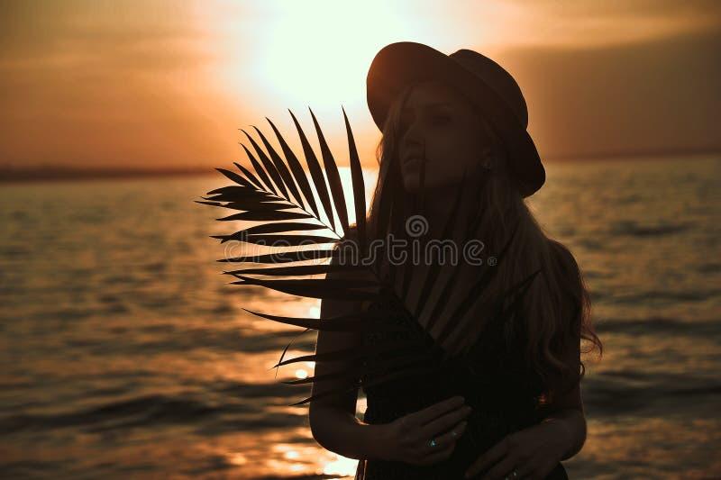 La belle femme élégante dans le chapeau avec la palmette dans des mains a un amusement sur la plage au coucher du soleil image libre de droits