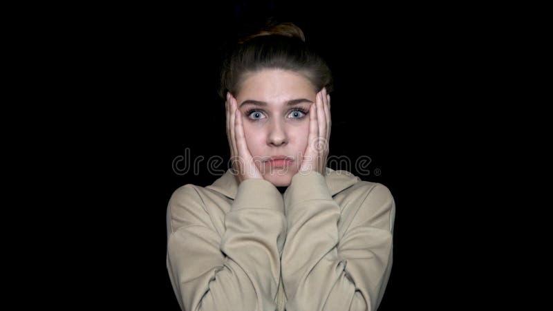 La belle femme étonnée tient des joues par ses mains, d'isolement sur le fond noir Jeune femme choquée photo stock