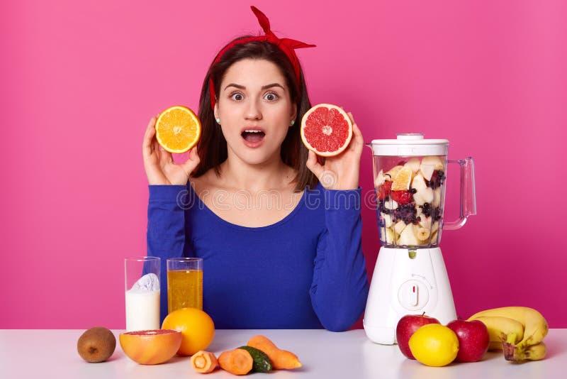 La belle femme étonnée tient la tranche d'orange et le pamplemousse, a choqué l'expression, ouvre la bouche de la stupéfaction, e photos libres de droits