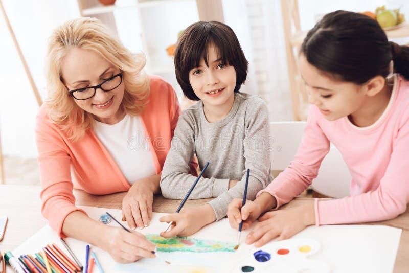 La belle femme agée enseigne des enfants à dessiner Aspiration de petits enfants Leçons de dessin photographie stock libre de droits
