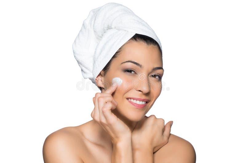 La belle femme applique la lotion à son visage photo stock