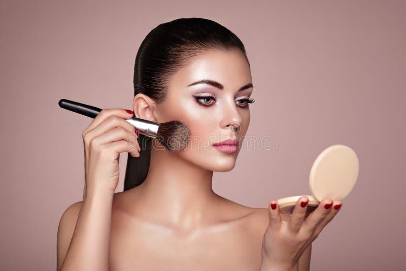 La belle femme applique le teint avec la brosse image stock