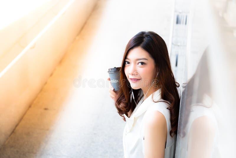 La belle femme asiatique avec du charme tient une tasse de papier de cof chaud images stock