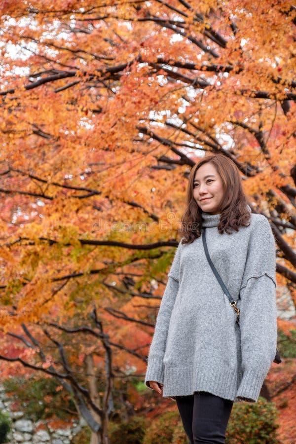 La belle femme asiatique a eu plaisir à se tenir dans le jardin avec des feuilles d'arbre rouge et orange à l'arrière-plan d'auto photo stock