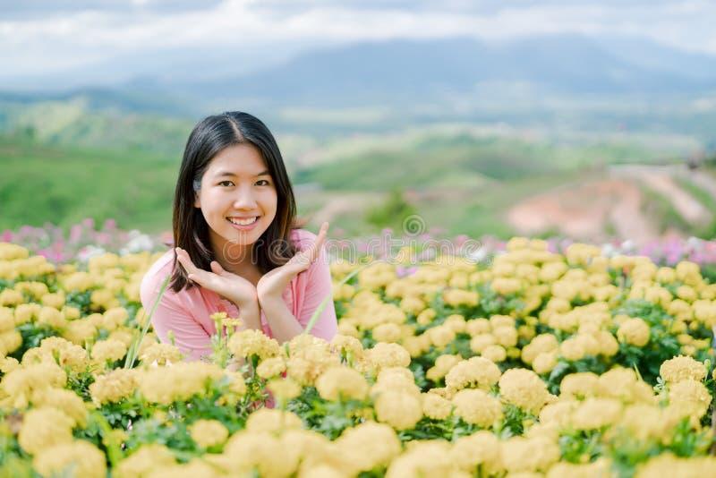 La belle femme asiatique utilisant une chemise rose se tenant heureusement souriante dans un jardin d'agrément jaune derrière est images stock