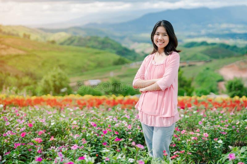 La belle femme asiatique utilisant une chemise rose souriant heureusement dans le jardin d'agrément rose derrière est un Mountain image libre de droits