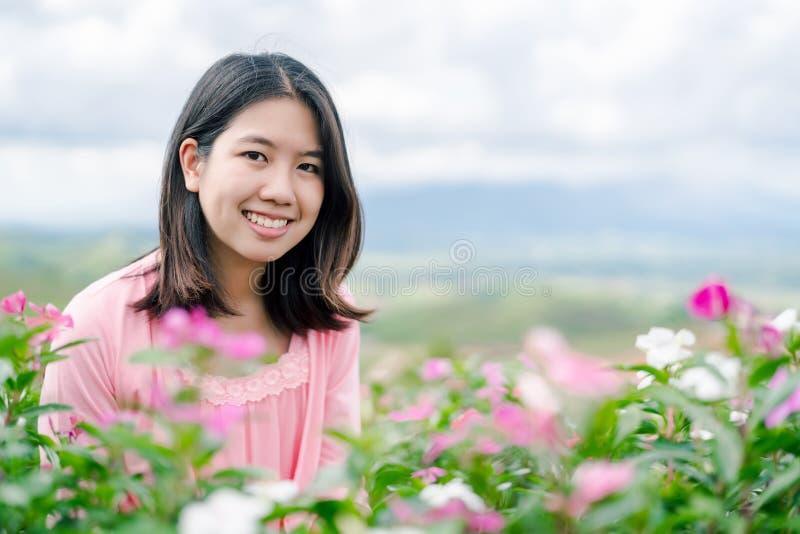 La belle femme asiatique utilisant une chemise rose souriant heureusement dans le jardin d'agrément rose derrière est un Mountain photos stock