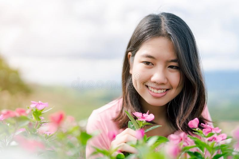 La belle femme asiatique utilisant une chemise rose souriant heureusement dans le jardin d'agrément rose derrière est un Mountain photographie stock