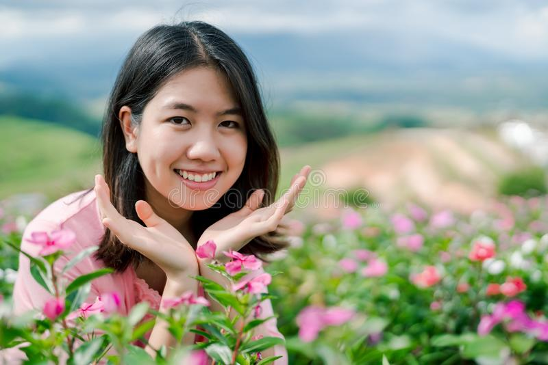 La belle femme asiatique utilisant une chemise rose souriant heureusement dans le jardin d'agrément rose derrière est un Mountain image stock