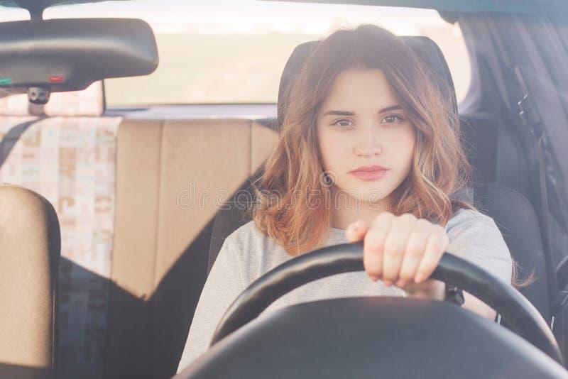La belle femme assurée dans des commandes de transport voiture, étant attentive sur la route, s'assied derrière la roue, a le reg image libre de droits