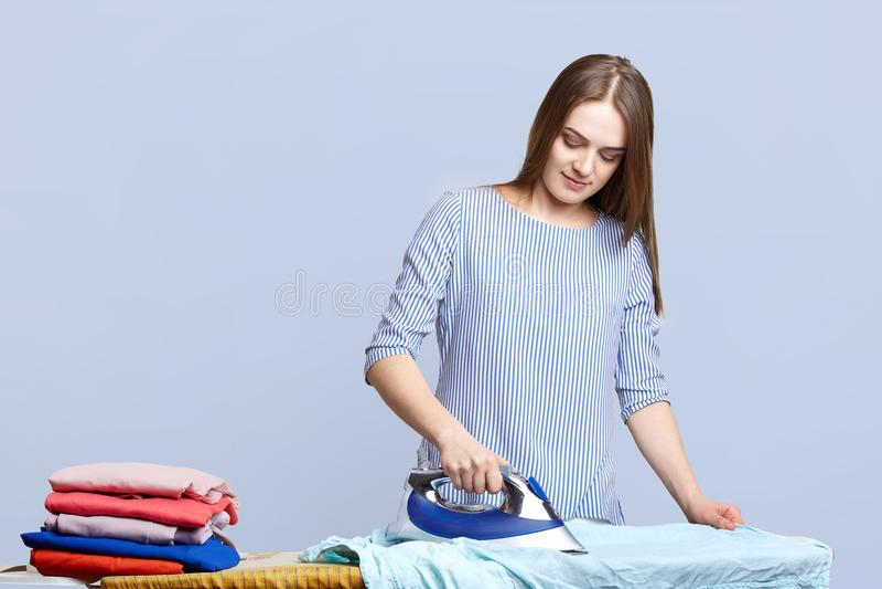 La belle femme au foyer de brune repasse des vêtements sur des planches à repasser, le carillonne d'une manière ordonnée, étant o images libres de droits