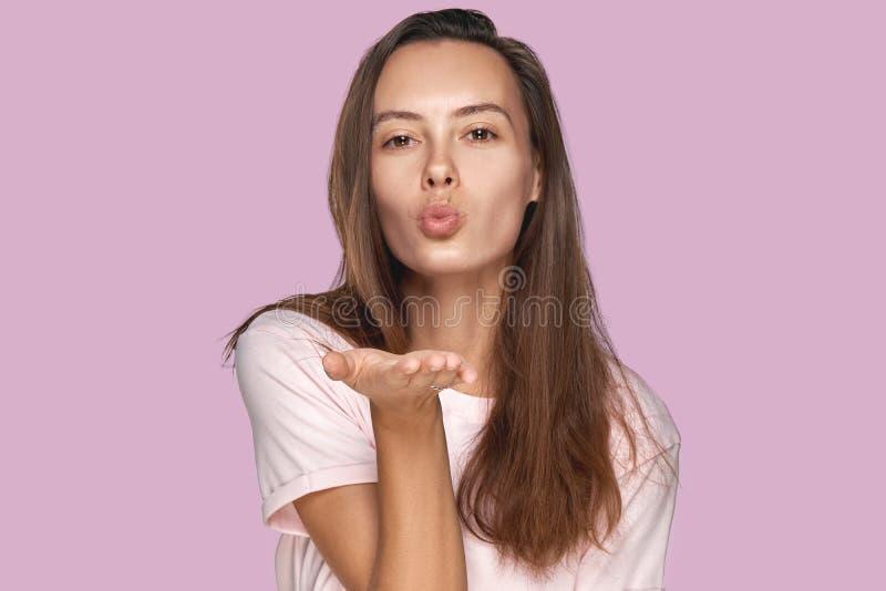 La belle femme avec de longs coups baiser de cheveux foncés, démontre ses bons sentiments, dit au revoir sur la distance Jeune jo photo libre de droits