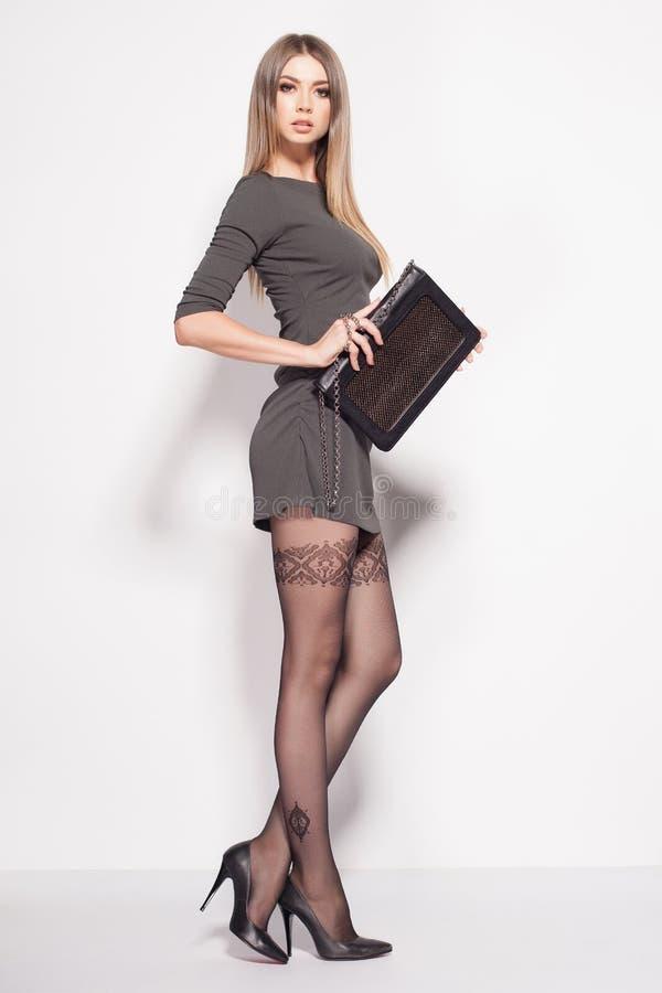 La belle femme avec de longues jambes sexy a habillé la pose élégante dans le studio photo stock