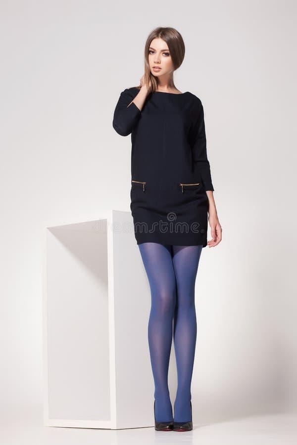 La belle femme avec de longues jambes sexy a habillé la pose élégante dans le studio photographie stock