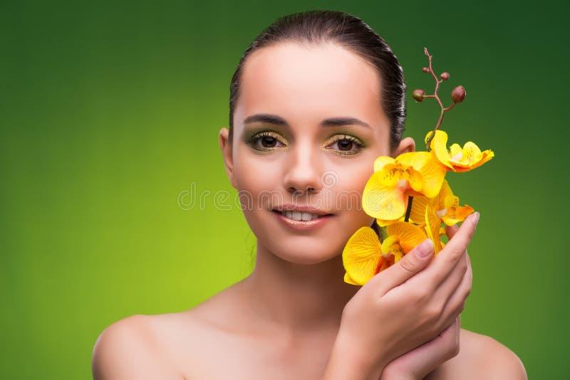 La belle femme avec la fleur jaune d'orchidée images stock