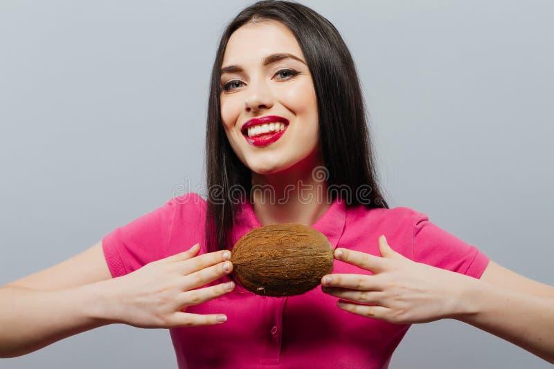 La belle femme avec la noix de coco remet dedans le fond gris images stock