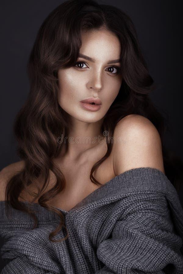 La belle femme avec la peau et les cheveux sains se courbe, posant dans le studio Visage de beauté photographie stock libre de droits