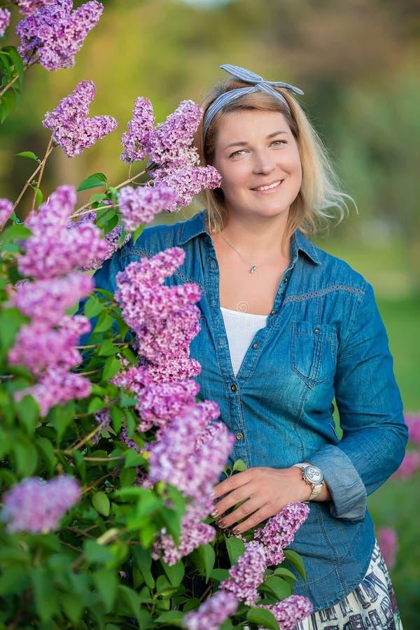 La belle femme avec le groupe lilas et la guirlande des fleurs font du jardinage au printemps, portrait de jeune mère enceinte images stock