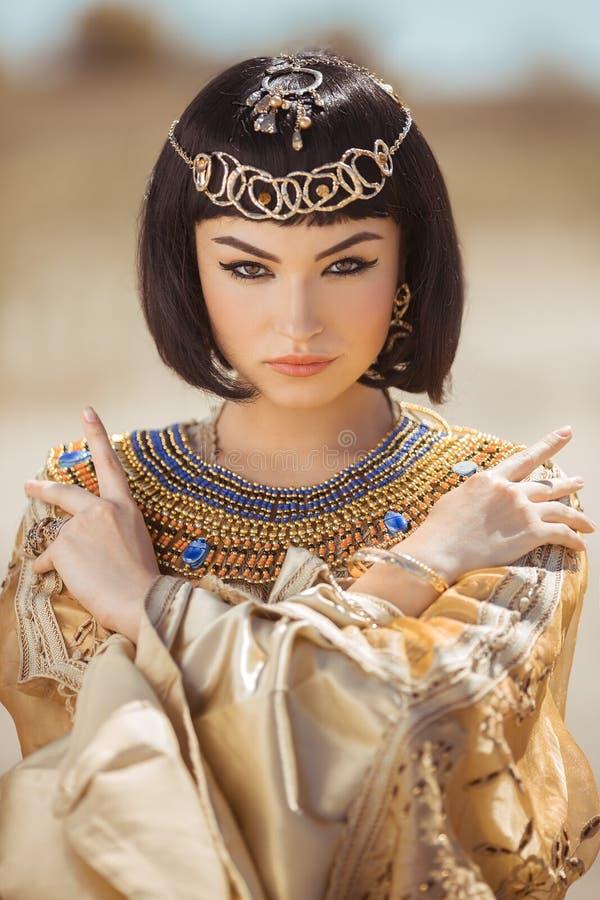 La belle femme avec le maquillage de mode et la coiffure aiment la Reine égyptienne Cléopâtre dehors contre le désert images stock
