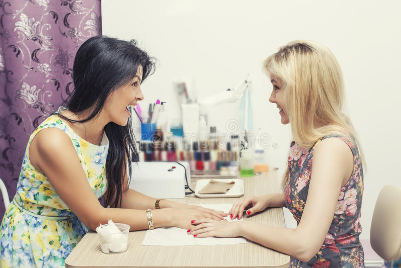 La belle femme avec le salon de beauté le client fait le manikpur images stock