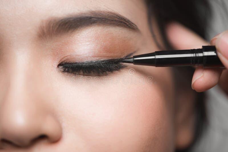 La belle femme avec lumineux composent l'oeil avec le maquillage noir de revêtement images libres de droits