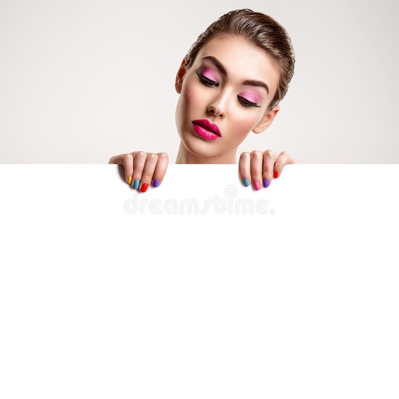 La belle femme avec une manucure colorée tient l'affiche vide images libres de droits