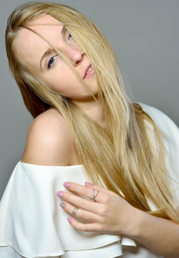 La belle femme blonde avec de longs cheveux de soufflement avec naturel font image stock