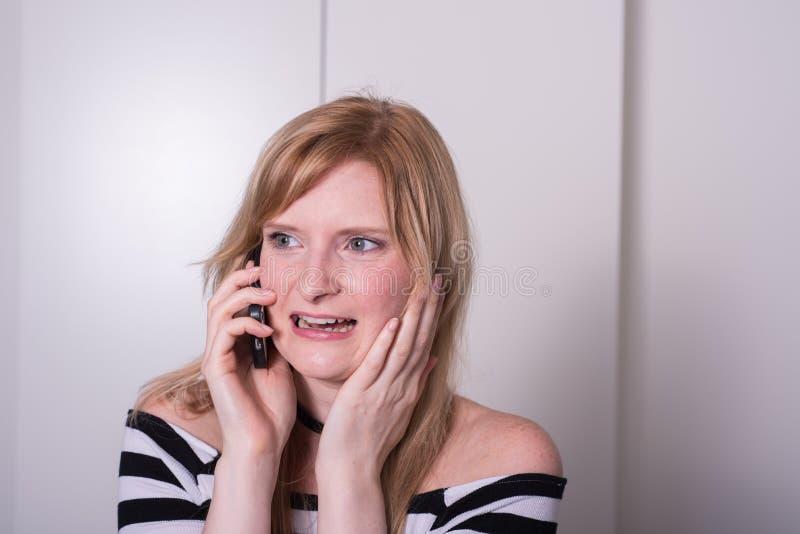 La belle femme blonde est très bouleversée pendant un appel téléphonique image stock