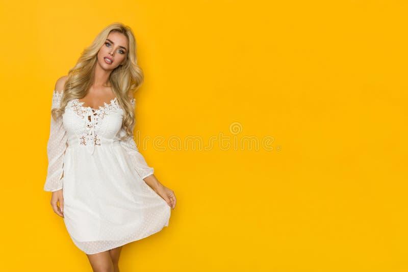La belle femme blonde pose dans Mini Dress blanc image libre de droits
