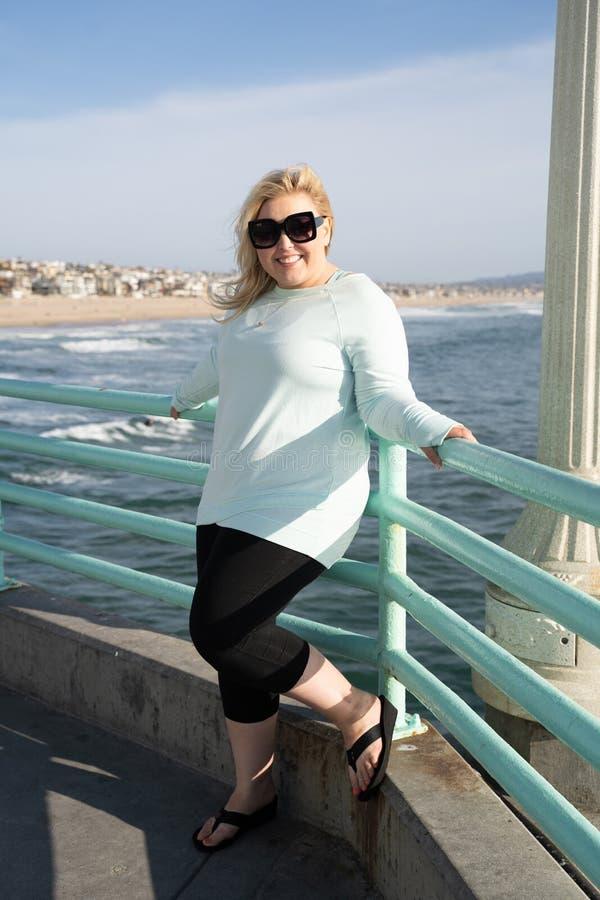 La belle femme blonde pose sur le pilier de Manhattan Beach la Californie vers la fin du soleil d'après-midi Pleine verticale de  image stock