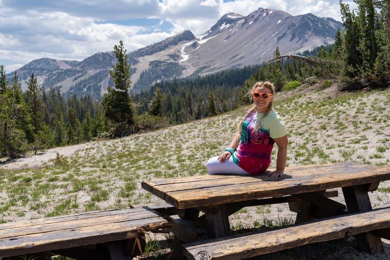 La belle femme blonde s'assied sur une table de pique-nique au point de vue de vue de minaret dans les lacs gigantesques la Calif images libres de droits