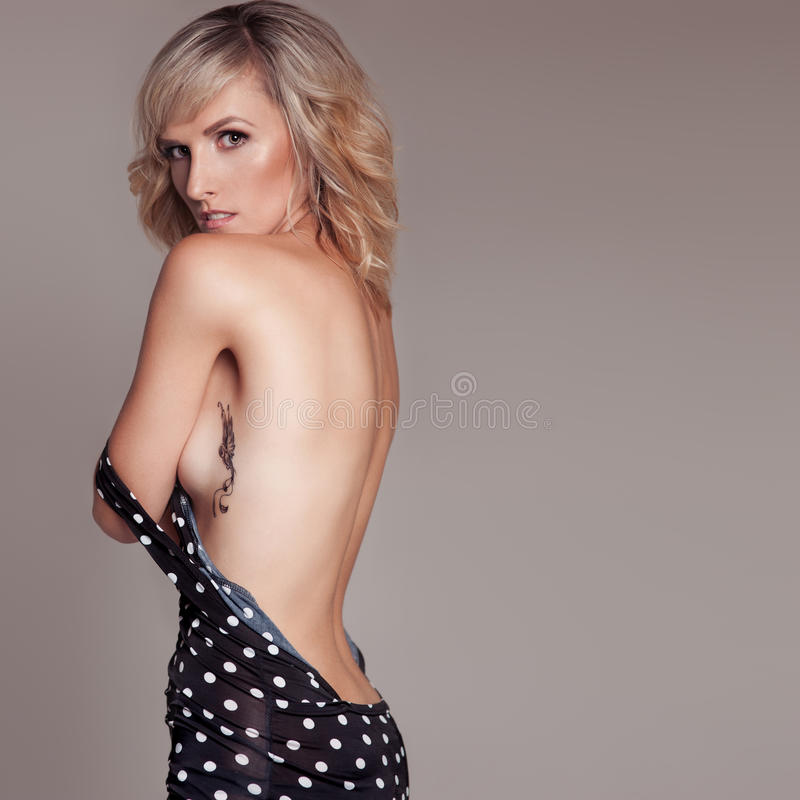 La belle femme blonde sexy dans la robe à pois noire avec dénudé de retour tatouent le colibri d'oiseau de son côté dans le studi images stock