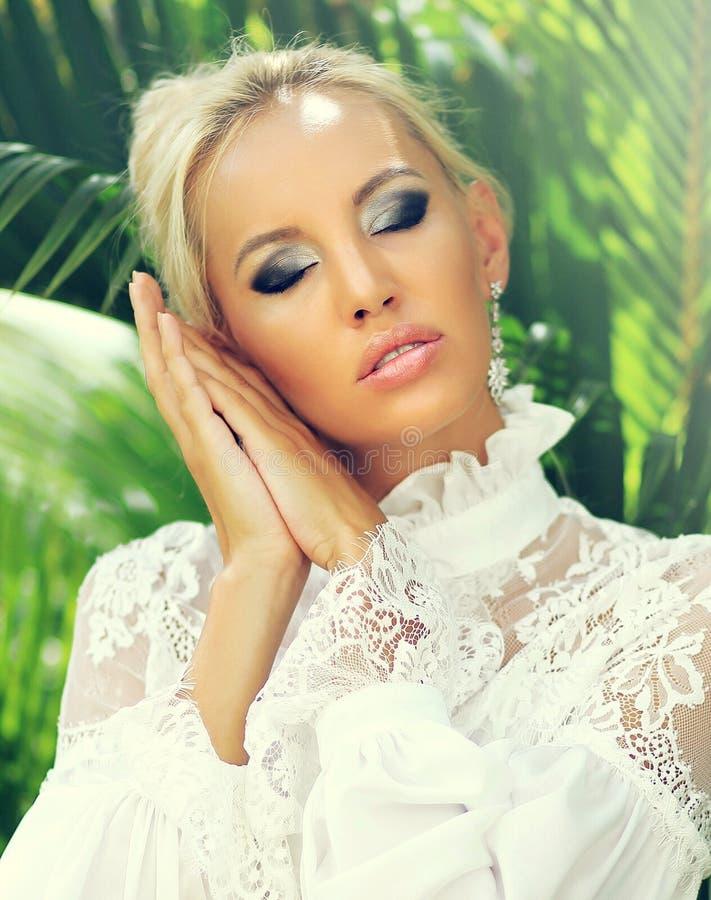 La belle femme blonde stupéfiante avec des yeux s'est fermée image stock