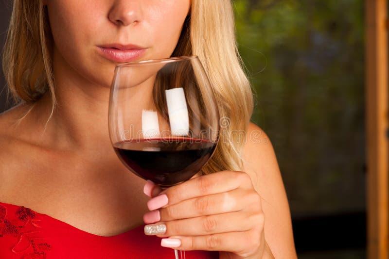 La belle femme boit du vin rouge extérieur sur un afternoo chaud d'été images libres de droits