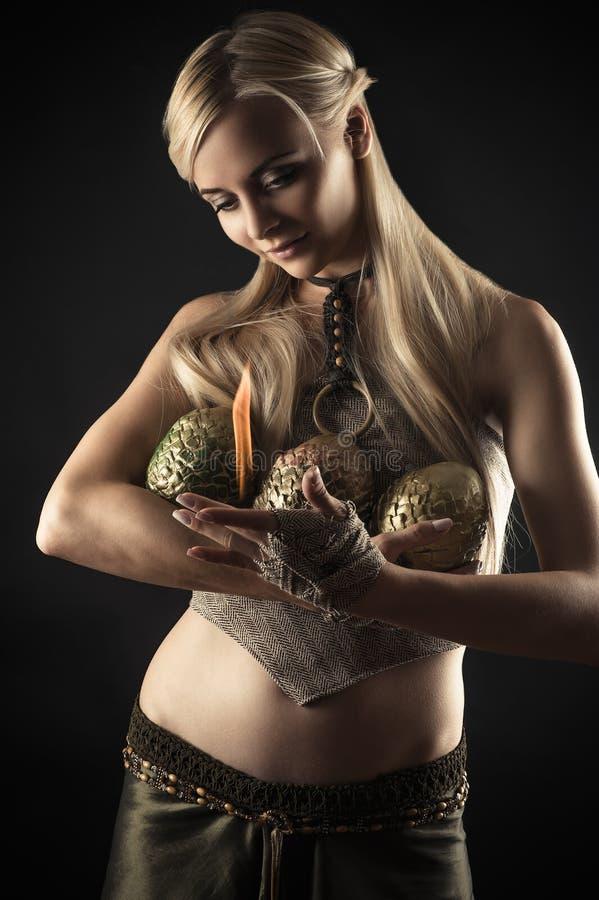 La belle femme chauffe des oeufs de dragon du feu photographie stock libre de droits