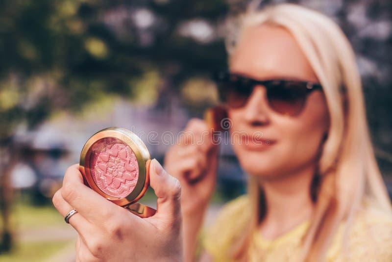 La belle femme corrige le maquillage dans la rue Foyer sur la palette de poudre image libre de droits